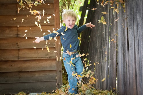 little boy running through grass throwing leaves in the air in Cokato MN